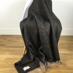 belgravia charcoal grey & beige herringbone blanket draped over chair